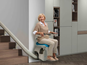 Elderly lady ascending flight of stairs on a curved stair lift.